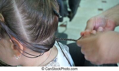 Hairdresser hands weaving a dreadlocks for little girl