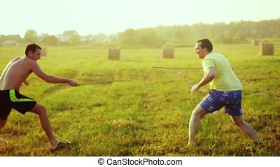 Young friends play the fool in the field during sunset with...