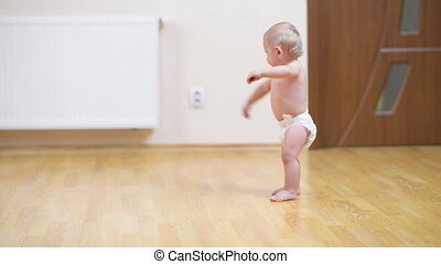 Baby making his first steps on the floor at home