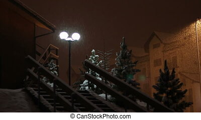 Snowing at night on the background of a lamppost.
