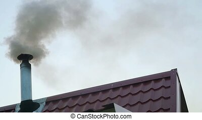 Smoking chimney on the roof of a house in front of the...