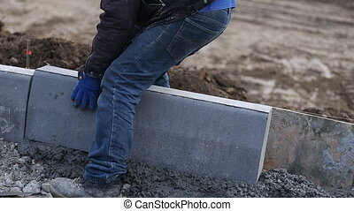 worker puts a curb close-up