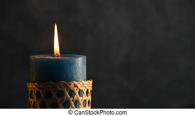 Blue candle trembling flame with grey background and blown...