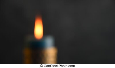 Blue candle trembling flame with grey background focusing in...