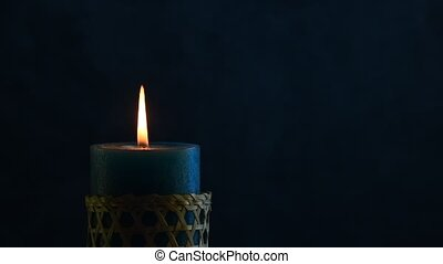 Blue candle trembling flame with blue background blown out -...