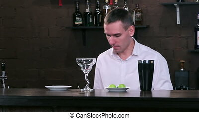 Bartender at work behind the bar - The man puts the...