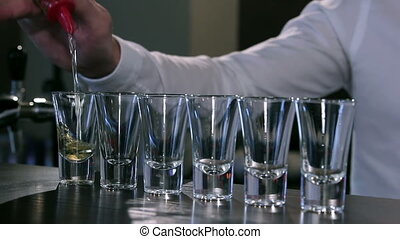 The bartender makes a shot set - A guy pours the alcohol...