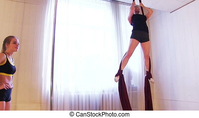 Aerial Gymnast Workout - Young beauty woman is practicing...