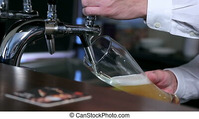 Filling of beer into a glass - Beer is poured into a glass...