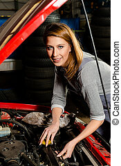 Young female trainee fixing car engine in garage - Portrait...