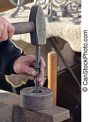 Hands of a blacksmith working with his hammer - The hands of...
