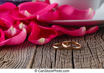 Golden rings and rose petals on rustic wood - Wedding...