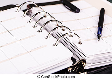 Personal organizer or planner with pen on white background -...