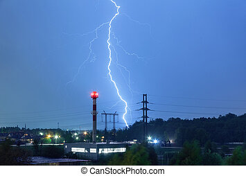 Lightning in the night sky over the boiler house and power lines