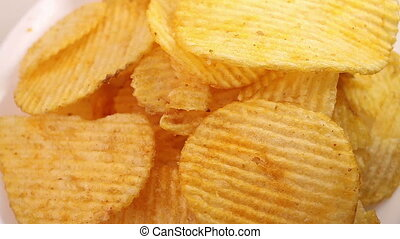 Potato chips heap rotating over white background, macro view