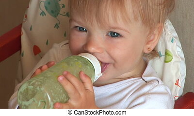 Child drinks milk from a bottle