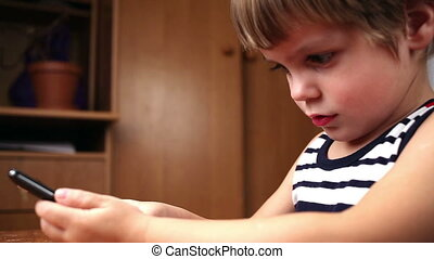 Little boy playing and touching a mobile phone