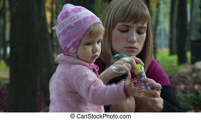 Mother and child in the park blow bubbles