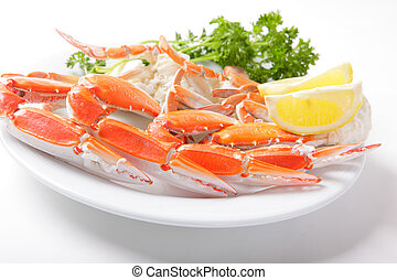 Crab legs with lemon and parsley isolated on white