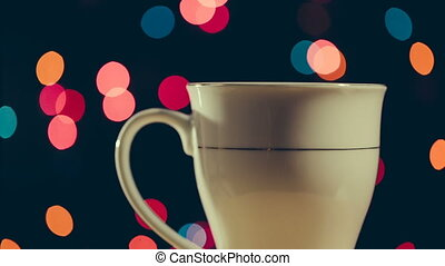 Hot beverage in the cup rotate around its axis on bokeh...