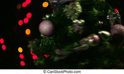 Dressed christmas tree rotate around its axis on bokeh background.