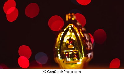 Gold christmas toy revolves around its axis  on a bokeh background.