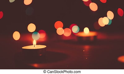 Two candles burning on a bokeh background.