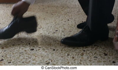 man in white wedding shirt puts on black shoes ties...