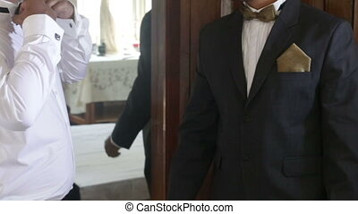 man helps groom to put on bowtie in front of mirror - man in...