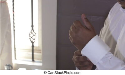 man buttons up white wedding shirt cuffs with cufflinks...