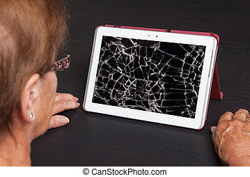 Senior lady with tablet, cracked screen, concept of...