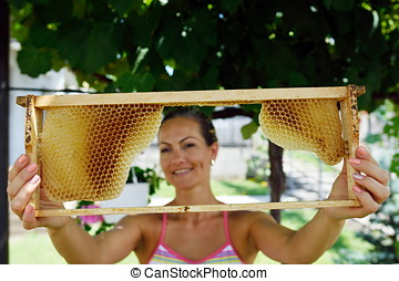 young woman holding frame with honeycomb - young smiling...