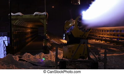 Snow cannons are working at night - Snow guns producing snow...
