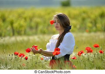 young beautiful woman on cereal field with poppies in summer...