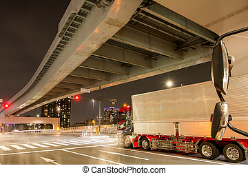 Stopped semi trailer truck and overpass in Tokyo at night
