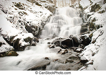 Waterfall mountain river in a forest in winter