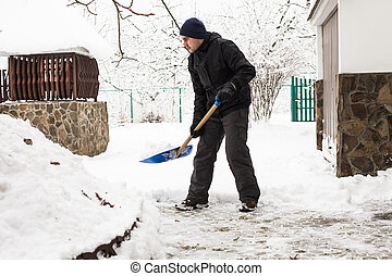 The Snow removal - Young man remove snow near the suburban...