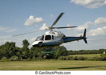 Helicopter taking off or landing in a field - Blue and white...