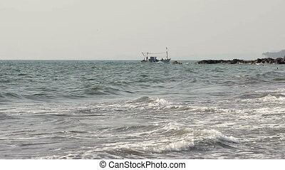 commercial fishing boat on the horizon