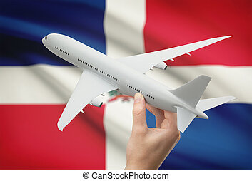 Airplane in hand with flag on background - Dominican...