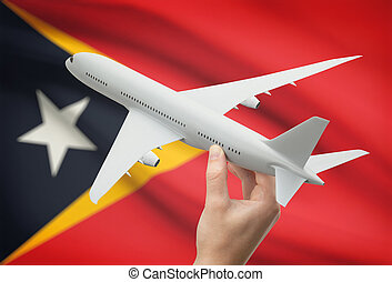 Airplane in hand with flag on background - East Timor -...