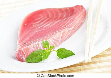 Raw tuna steak on white plate with chopsticks
