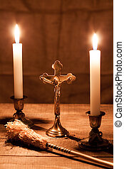 Gold cross with candles and sprinkler on wooden background...