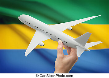 Airplane in hand with flag on background - Gabon - Airplane...