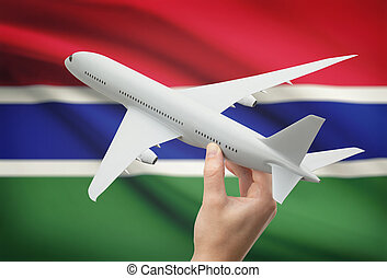 Airplane in hand with flag on background - Gambia - Airplane...