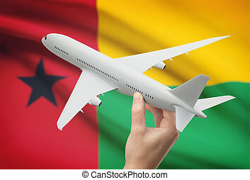 Airplane in hand with flag on background - Guinea-Bissau -...