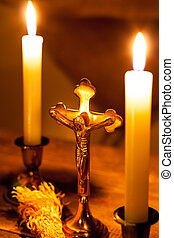 Gold cross with candles and sprinkler on wooden background....