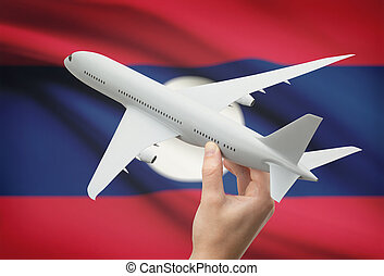 Airplane in hand with flag on background - Laos - Airplane...