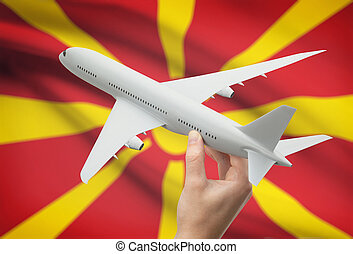 Airplane in hand with flag on background - Macedonia -...