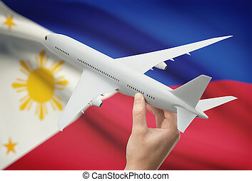 Airplane in hand with flag on background - Philippines -...
